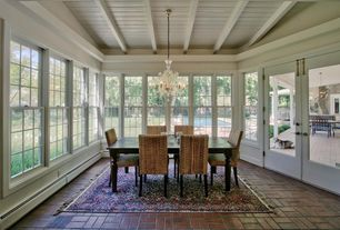 Traditional Dining Room with French doors, Brick floors, Exposed beam, Chandelier