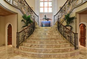 Mediterranean Staircase with Wainscotting, Arched window, travertine tile floors, High ceiling