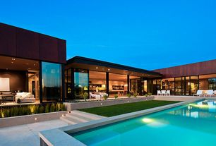 Modern Swimming Pool with Raised beds, Casement, White outdoor furniture, exterior stone floors, sliding glass door, Lap pool
