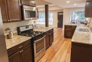 Craftsman Kitchen with Hardwood floors, Flat panel cabinets, partial backsplash, can lights, specialty door, Standard height