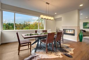 Modern Dining Room with stone fireplace, can lights, picture window, Pendant light, Paint, Fireplace, Linon Cowhide Rug