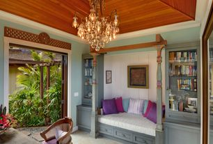 Tropical Living Room with Cathedral ceiling, Concrete floors, Built-in bookshelf, Columns, Chandelier