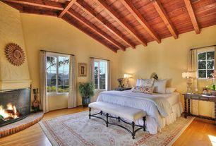 Mediterranean Master Bedroom with metal fireplace, Hardwood floors, Exposed beam, High ceiling
