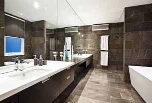 Contemporary Master Bathroom with stone tile floors, Corian counters, Bathtub, Freestanding, Casement, European Cabinets