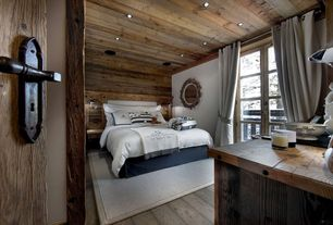 Rustic Guest Bedroom with Louvered door, Iron door hardware, Pottery barn cameron cotton grommet drape, Hardwood floors