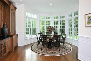 Traditional Dining Room with Built-in bookshelf, Crown molding, Wainscotting, Hardwood floors