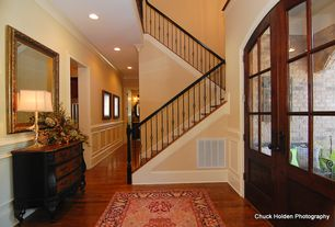 Traditional Entryway with High ceiling, Hardwood floors, Built-in bookshelf, Glass panel door, Wainscotting