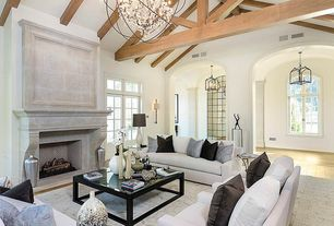 Cottage Living Room with High ceiling, Exposed beam, Wall sconce, Hardwood floors, Chandelier, Cement fireplace