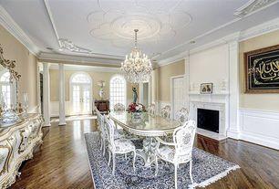 Traditional Dining Room with Hardwood floors, Glass panel door, Columns, Crown molding, Chandelier, Cement fireplace