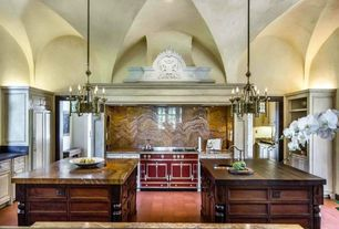 Mediterranean Kitchen with U-shaped, Custom hood, double oven range, can lights, Kitchen island, stone tile floors, Flush