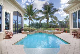Mediterranean Swimming Pool with exterior stone floors, Transom window, Pool with hot tub, Fence