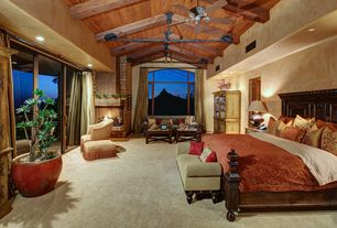 Mediterranean Master Bedroom with can lights, Ceiling fan, Arched window, Exposed beam, Fireplace, Carpet, stone fireplace