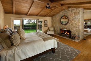 Eclectic Master Bedroom with metal fireplace, Fireplace, Hardwood floors, Standard height, Exposed beam, French doors