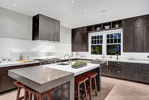 Contemporary Kitchen with Flat panel cabinets, Custom hood, limestone tile floors, Farmhouse sink, Flush, Breakfast bar