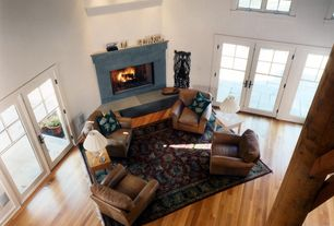 Contemporary Living Room with Casement, Cement fireplace, Hardwood floors, picture window, Fireplace, Columns, French doors