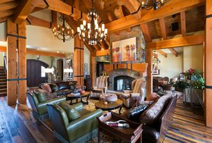 Rustic Living Room with Columns, stone fireplace, Hardwood floors, Chandelier, High ceiling, Exposed beam, specialty door
