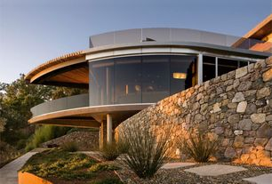 Contemporary Exterior of Home with Gravel landscape, Glass railing, Natural stone wall, Flagstone path, Cantilever balcony