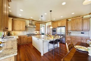 Traditional Kitchen with Hardwood floors, Casement, Built In Refrigerator, double wall oven, Wall Hood, full backsplash