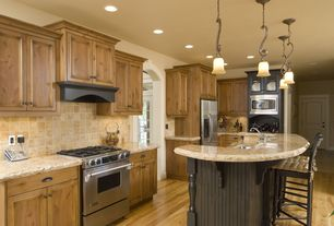 Craftsman Kitchen with Stone Tile, Mini-pendant with mojave glass, Simple granite counters, Hardwood floors, Breakfast bar