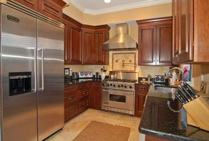 Traditional Kitchen with Crown molding, Galley, Raised panel, Standard height, Soapstone counters, Wall Hood, gas range
