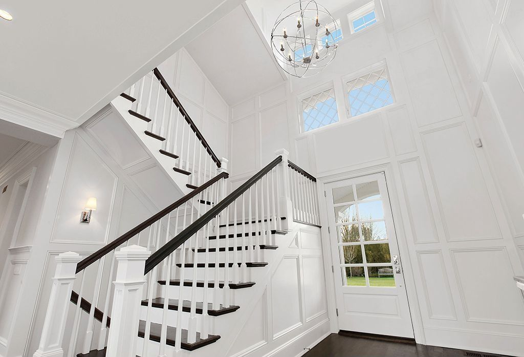 Contemporary Staircase with Wainscotting, Hardwood floors, Chandelier, Cathedral ceiling, French doors, Wall sconce