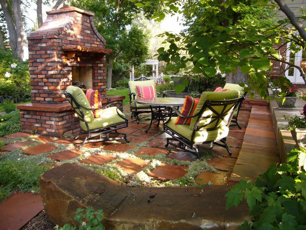 Traditional Exterior of Home with Trellis, Outdoor fireplace, Pathway, Raised beds, exterior stone floors, Outdoor dining set