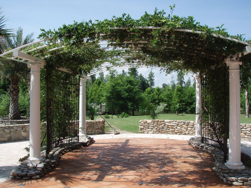 Tropical Landscape/Yard with Arched trellis, Ionic column, River rock wall