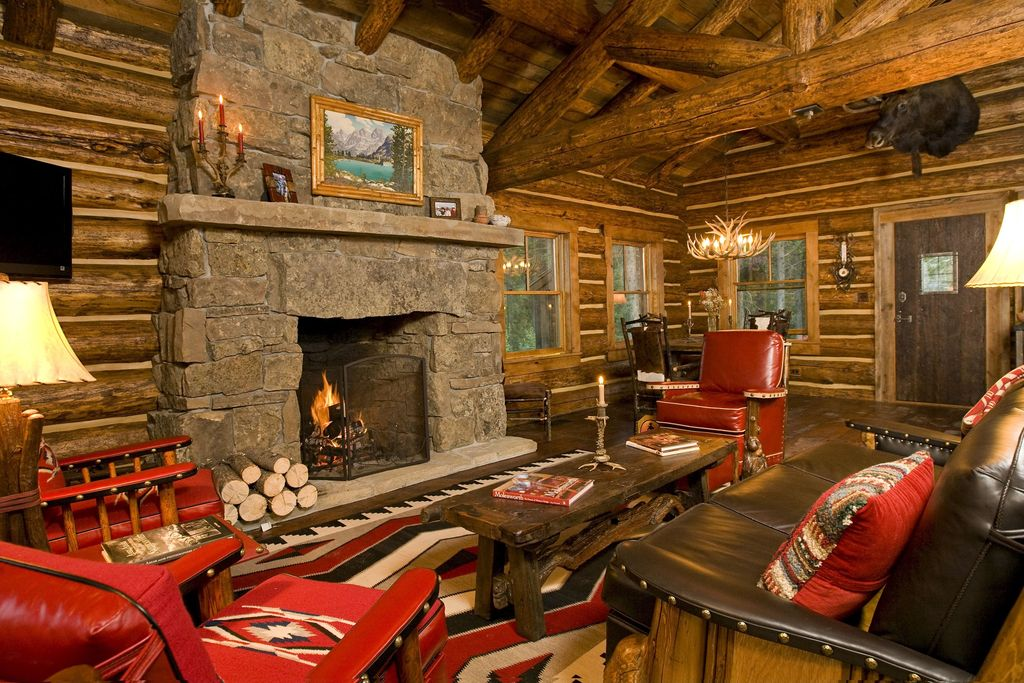 Rustic Living Room with High ceiling, Chandelier, Hardwood floors, Marc taggart & company burl club chair, stone fireplace