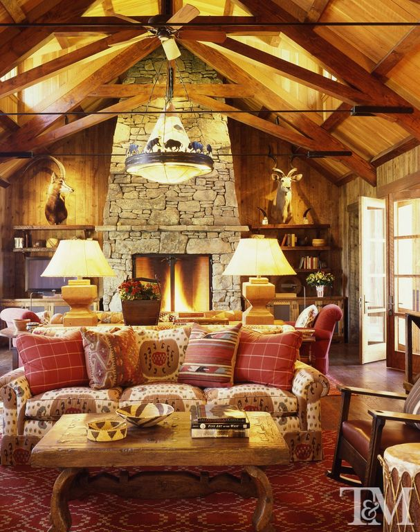 Rustic Living Room with L d burke of santa fe buffalo chandelier, Wood walls, Exposed trusses, stone fireplace, French doors