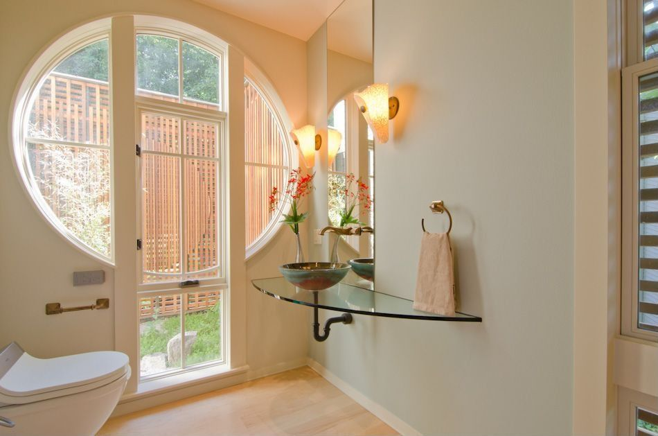 Modern Powder Room with Standard height, Vessel sink, Laminate floors, Glass counters, Wall sconce, Louvered door