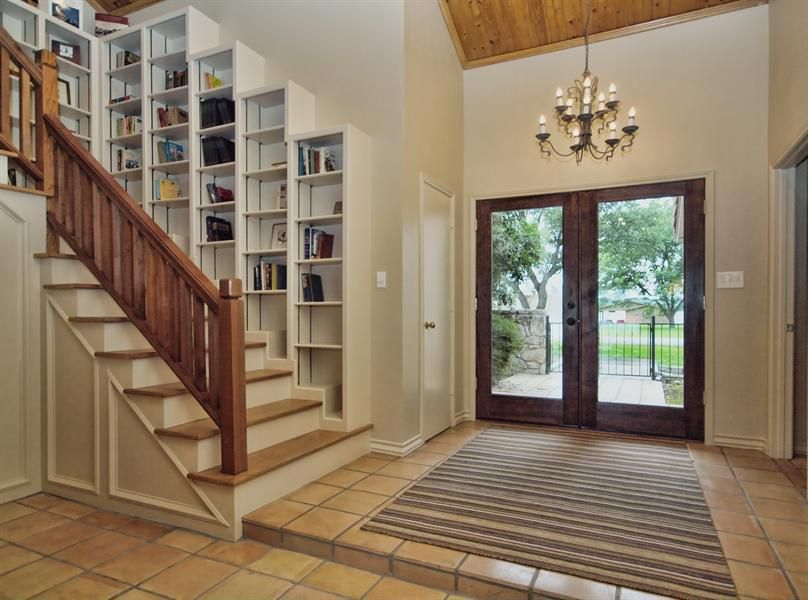 Traditional Entryway with stone tile floors, Built-in bookshelf, High ceiling, flat door, Crown molding, French doors