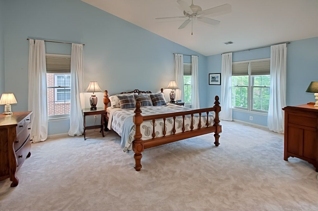Traditional Guest Bedroom with Ceiling fan, picture window, Standard height, Concrete floors