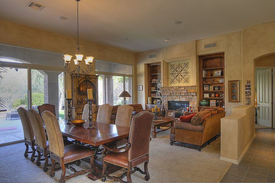 Eclectic Great Room with Transom window, Nailhead detail armchair, Pony wall, brick fireplace, Fireplace, Built-in bookshelf