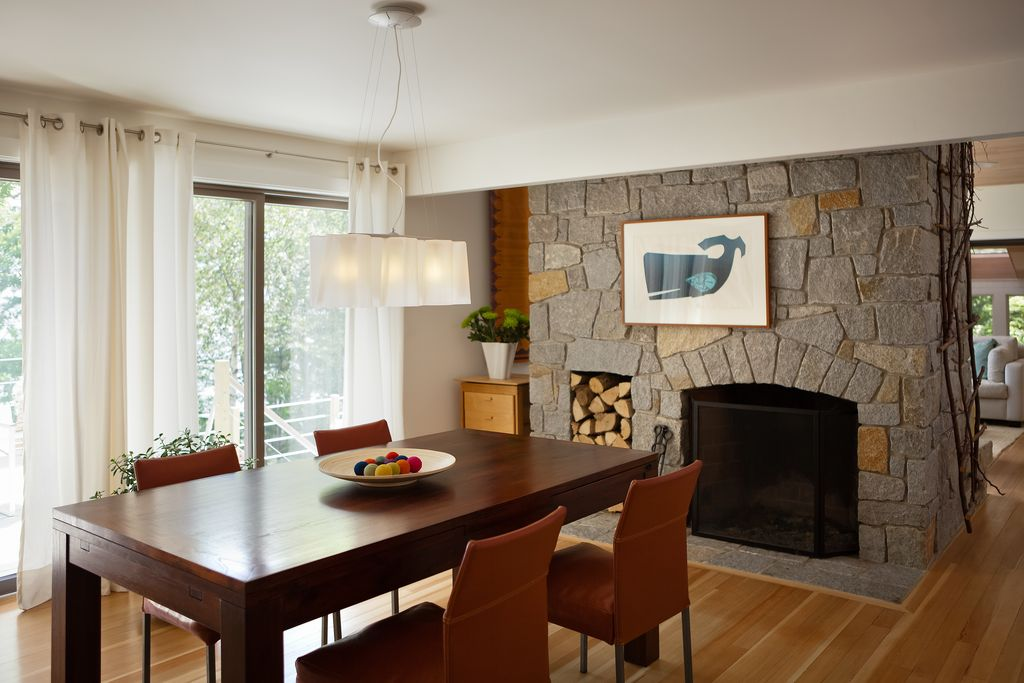 Contemporary Dining Room with stone fireplace, Standard height, Chandelier, Fireplace, Laminate floors, sliding glass door
