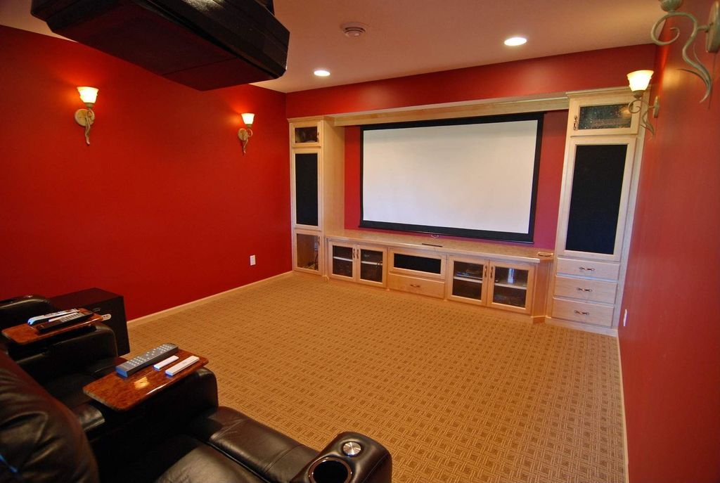 """Country Home Theater with Illuminati collection 23"""" high wall sconce, Paint 1, can lights, Built-in bookshelf, Wall sconce"""