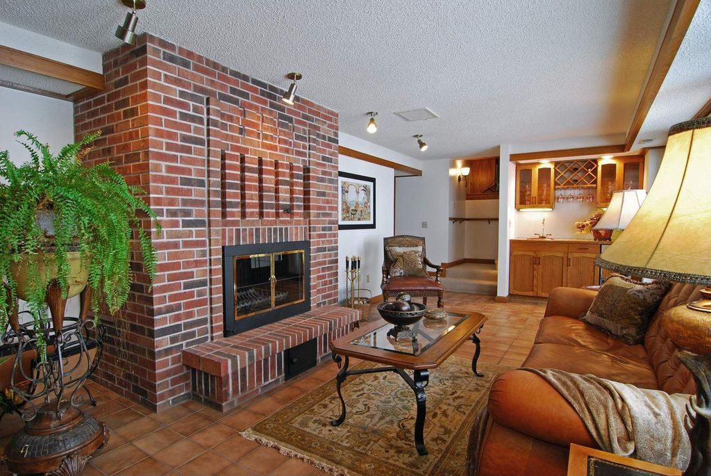 Craftsman Living Room with Standard height, Fireplace, brick fireplace, can lights, Crown molding, terracotta tile floors