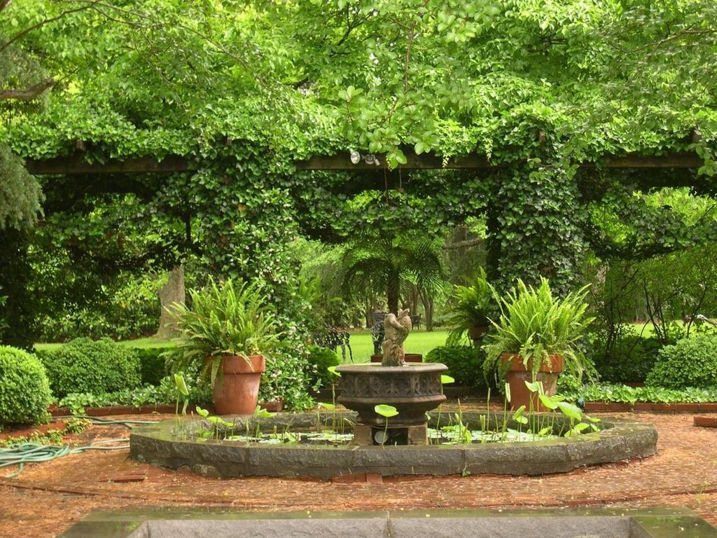 Traditional Landscape/Yard with Pond, Trellis, Fountain, exterior brick floors