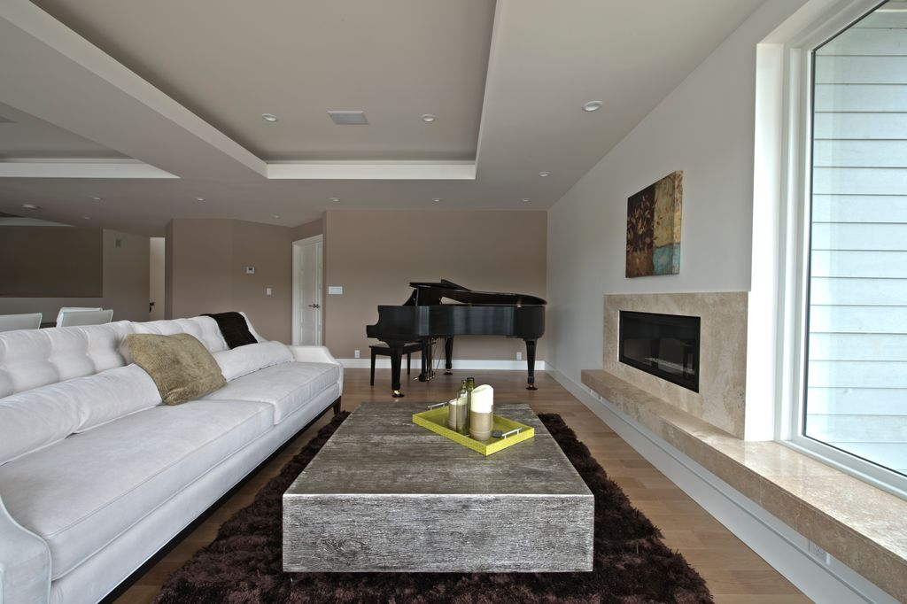 Contemporary Living Room with picture window, stone fireplace, Fireplace, sandstone floors, can lights, Standard height
