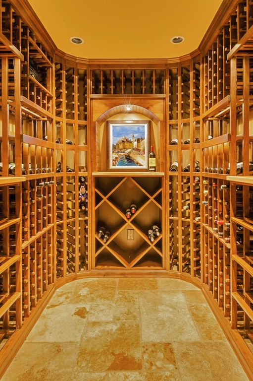 Mediterranean Wine Cellar with Crown molding, Standard height, can lights, limestone floors