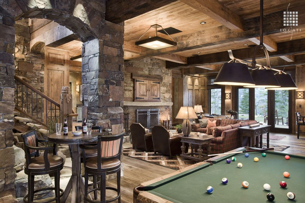 Country Game Room with Exposed beam, Wood panel ceiling, Stacked stone wall, High ceiling, Hardwood floors, Pendant light