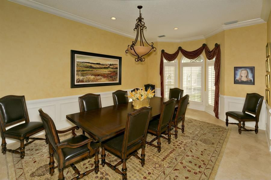 Traditional Dining Room with Pendant light, Wainscotting, Crown molding, Arched window, limestone tile floors