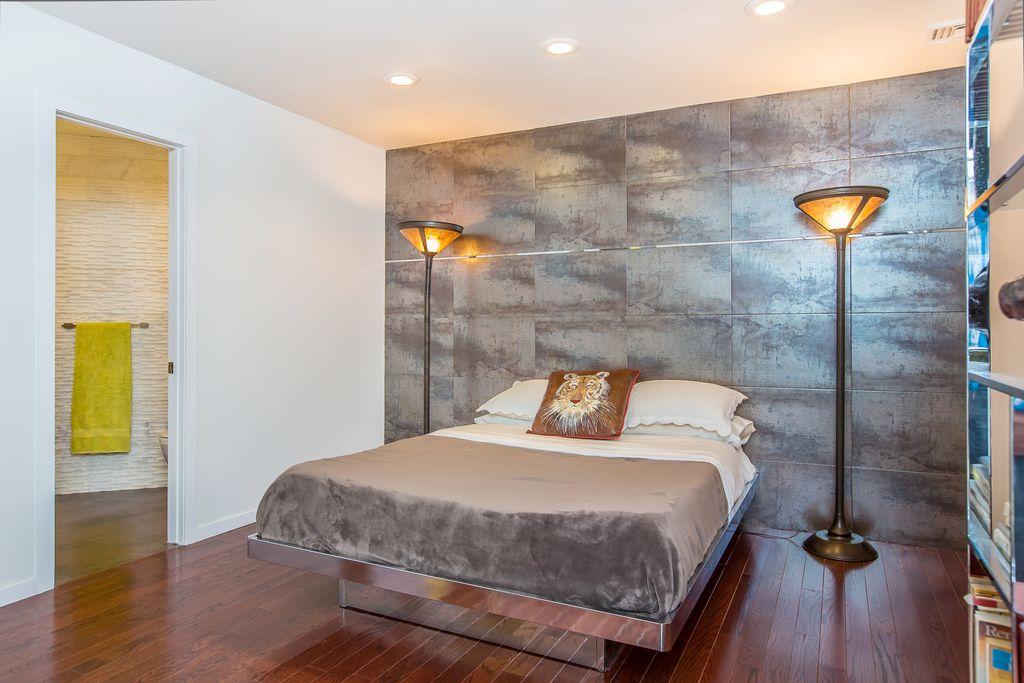 Contemporary Guest Bedroom with Built-in bookshelf, can lights, specialty door, Hardwood floors, Standard height