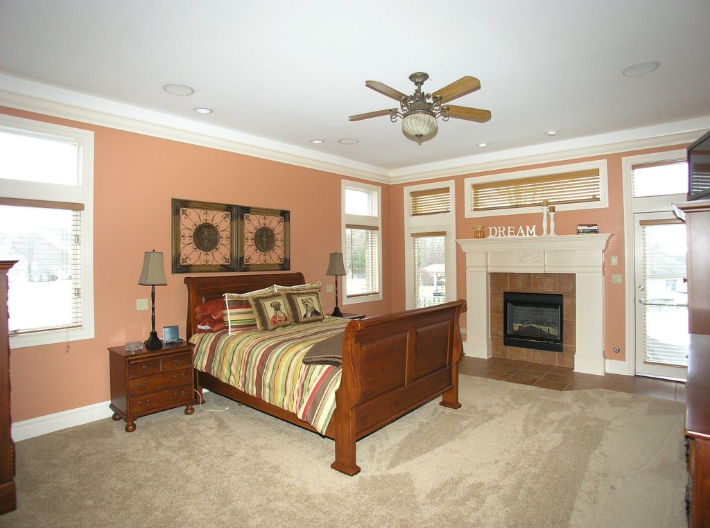 Country Master Bedroom with Built-in bookshelf, picture window, Ceiling fan, Transom window, Fireplace, can lights, Casement