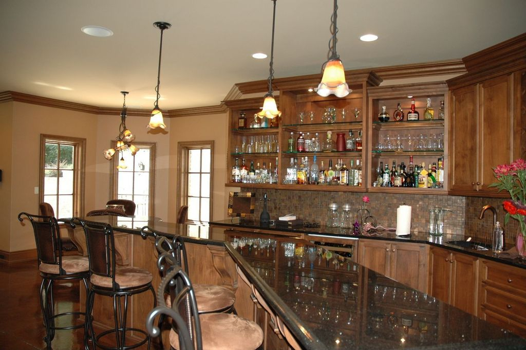 Traditional Bar with can lights, Chandelier, Pendant light, Crown molding, Concrete floors, Built-in bookshelf