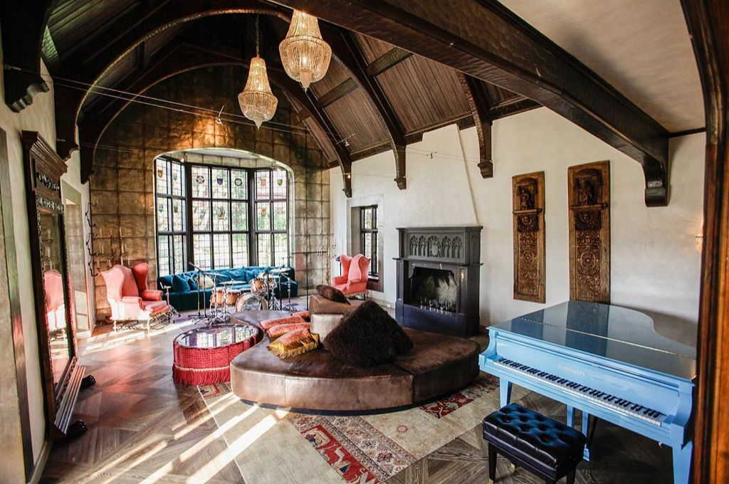 Eclectic Living Room with Hardwood floors, Chandelier, Cement fireplace, Chaucer wing chair, Fireplace, Bay window, Paint 1