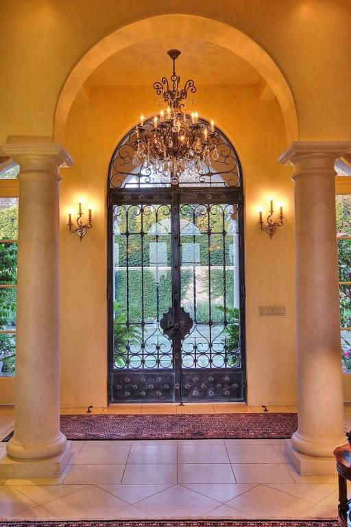 Mediterranean Entryway with stone tile floors, Columns, Wall sconce, Chandelier, Transom window, French doors, Arched window