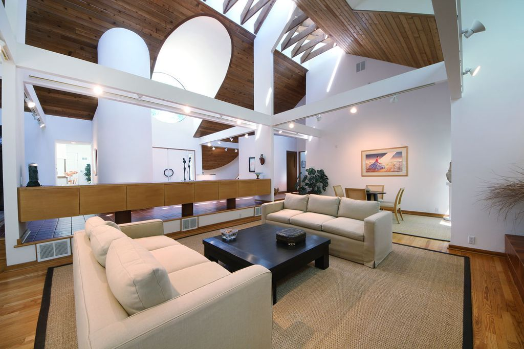 Contemporary Living Room with Cathedral ceiling, Built-in bookshelf, Hardwood floors, can lights, Exposed beam, Skylight