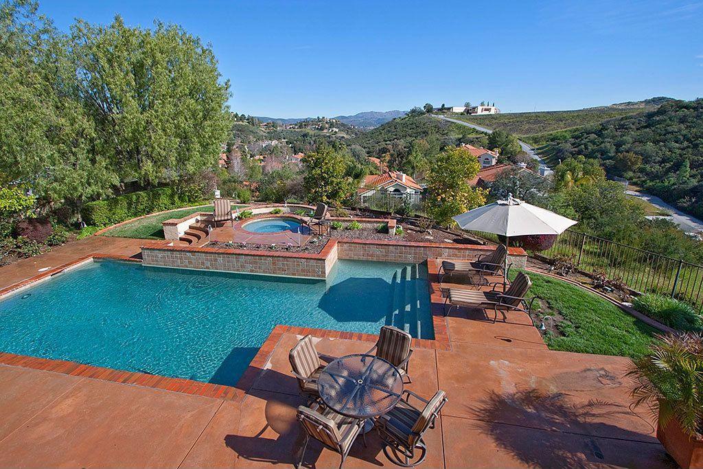Mediterranean Swimming Pool with Raised beds, exterior brick floors, exterior concrete tile floors, exterior tile floors