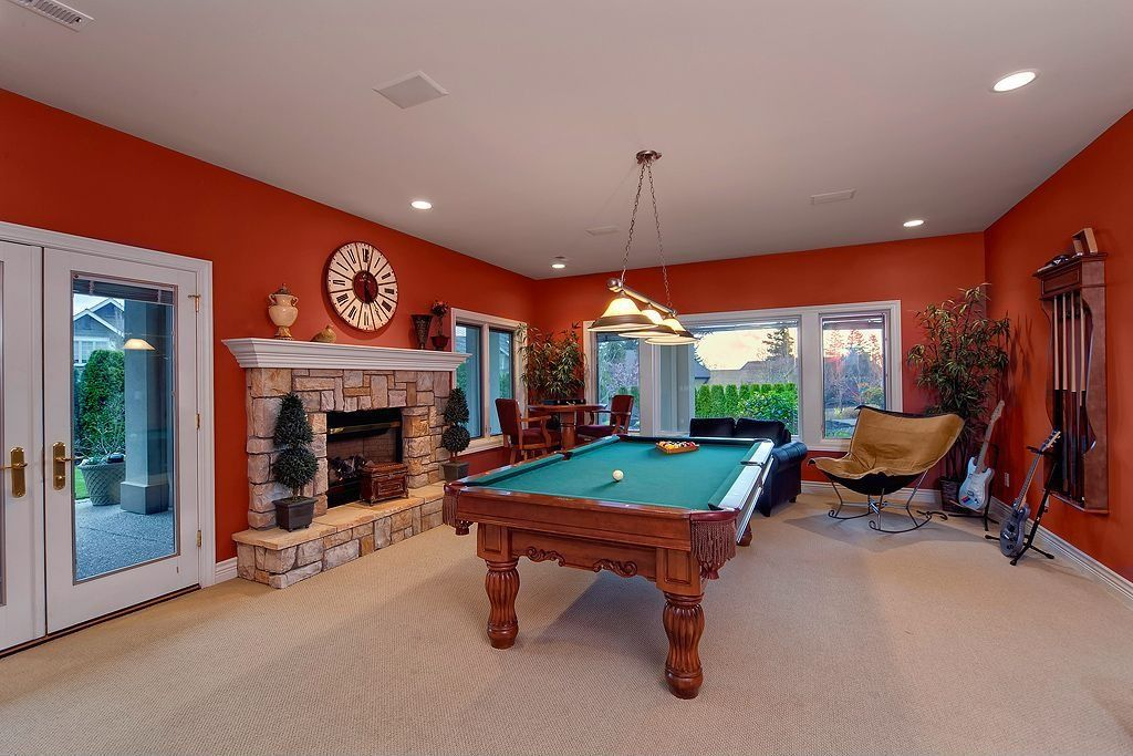 Eclectic Game Room with can lights, Fireplace, Casement, Pendant light, stone fireplace, Standard height, Carpet