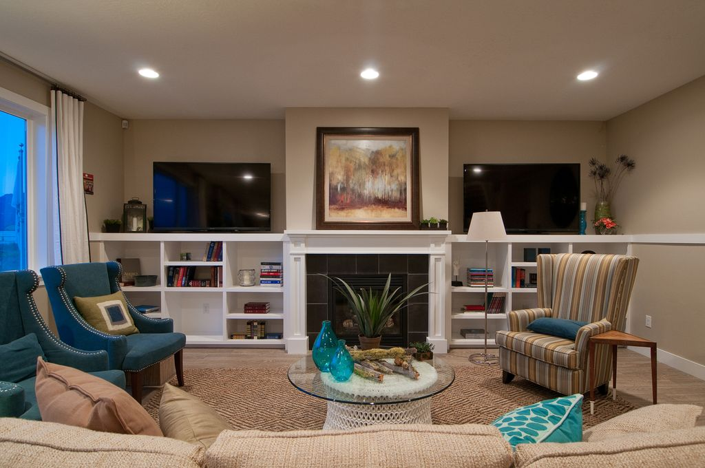 Contemporary Living Room with Built-in bookshelf, Laminate floors, stone fireplace